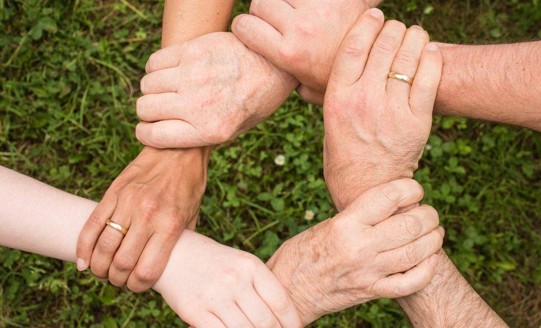 mãos de diferentes pessoas entrelaçadas em círculo